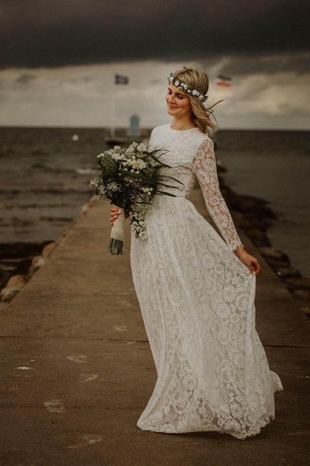 Braut während Hochzeitsshooting am Strand in Stein